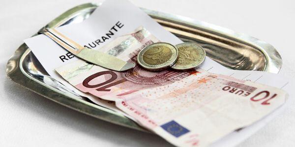 Conta de restaurante com moedas e notas em euros