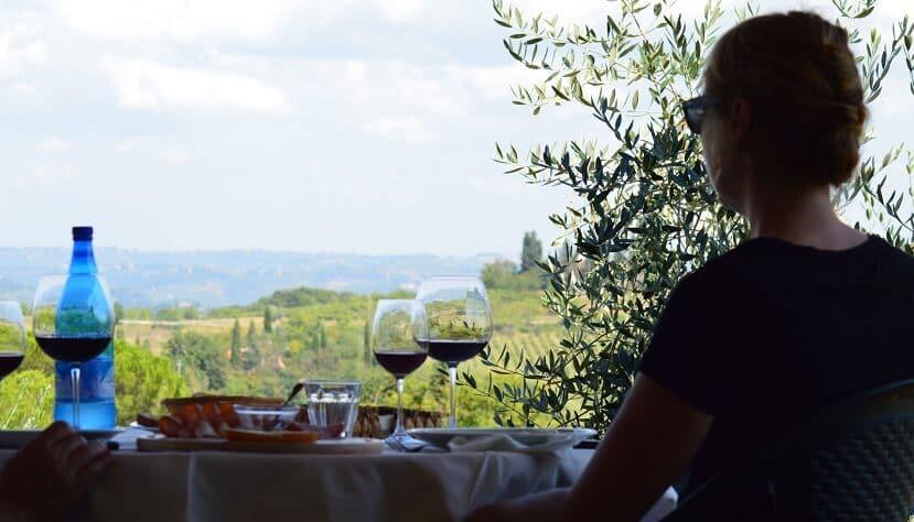 Pessoa sentada em mesa com taças de vinho