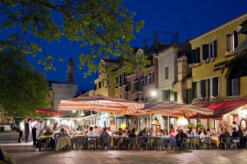 Pessoas no Campo di Santa Margherita a noite