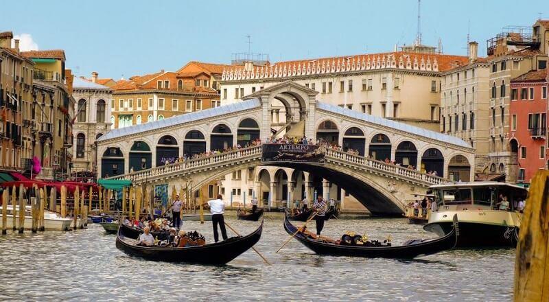 Gôndolas em canal e Ponte di Rialto ao fundo