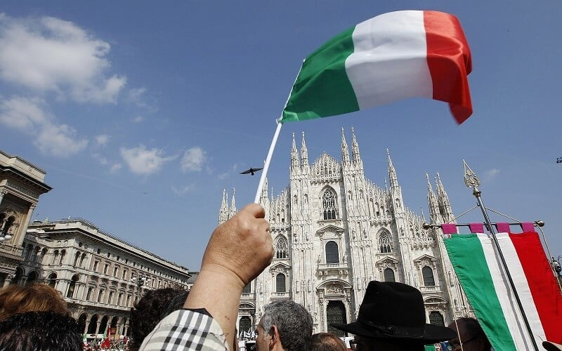 Bandeira italiana sendo segurada na frente do Duomo di Milão