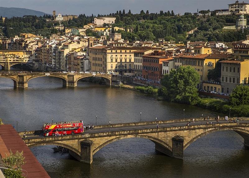 Ônibus turístico atravessando ponte de Florença