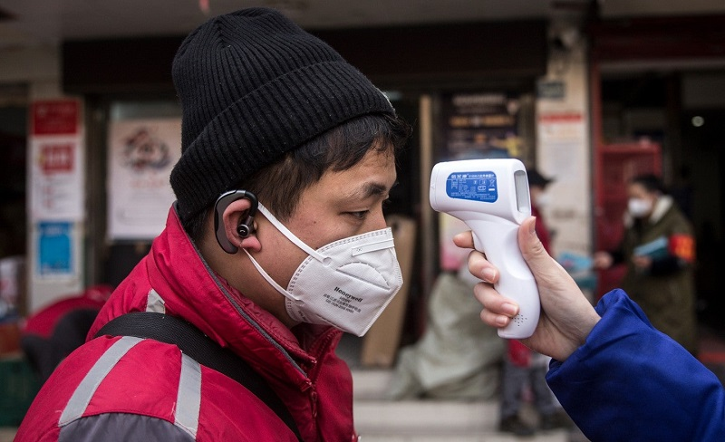 Homem com máscara tendo temperatura medida
